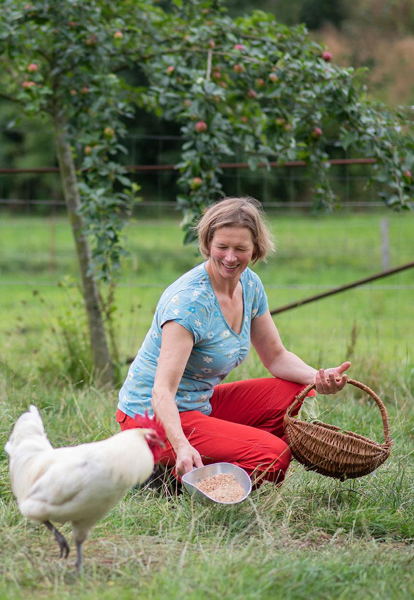 Anke Stoltenberg füttert ihre freilaufenden Hühner auf der Wiese