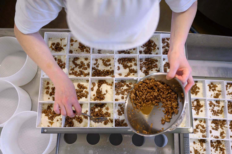Karo füllt in der Käserei Nüsse in den Camembert