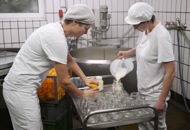 Karo und Anna verschöpfen in der Käserei Milch für Joghurt
