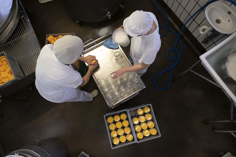 Karo und Anna verschöpfen in der Käserei Milch für den Joghurt