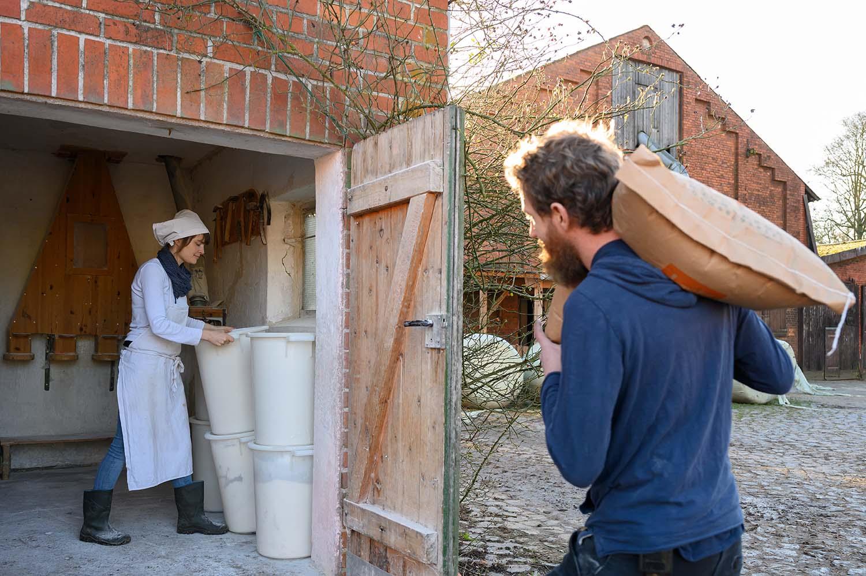 Philipp übergibt das Getreide an Verena in der Mühle