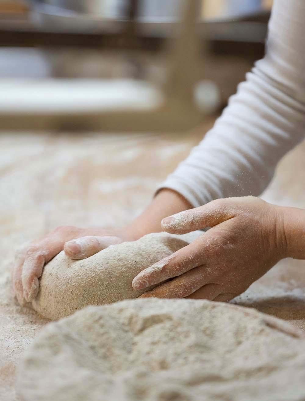 Bäckerin Verena knetet in der Backstube eine Portion Teig