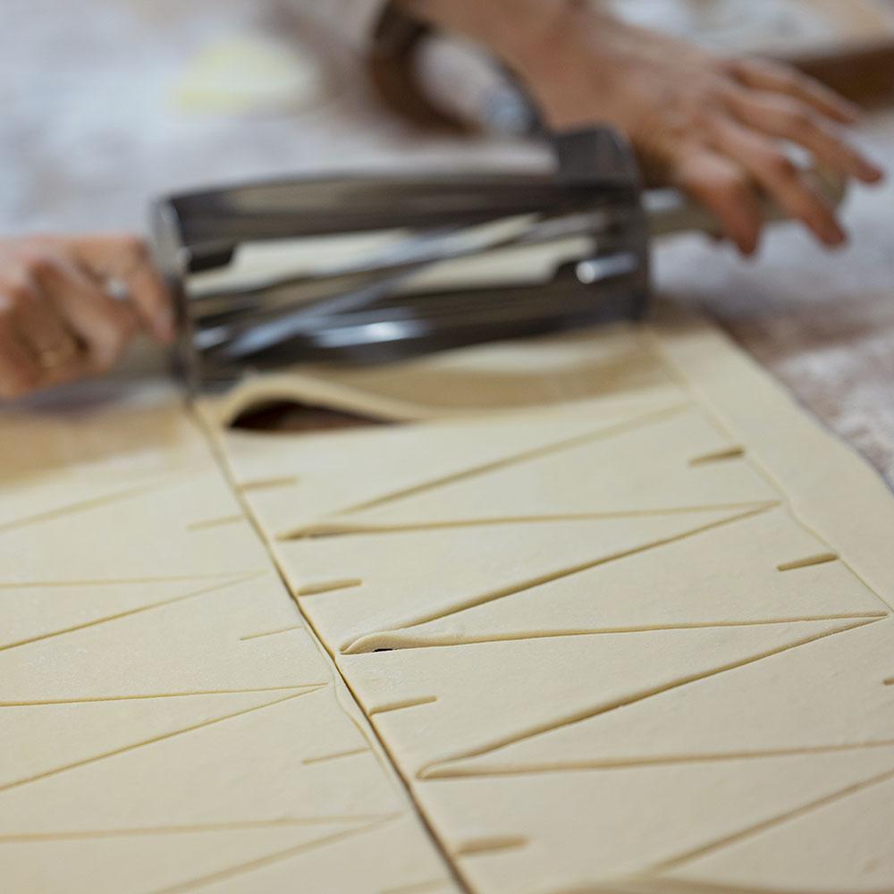 Bäckerin verena rollt in der Backstube Teig aus