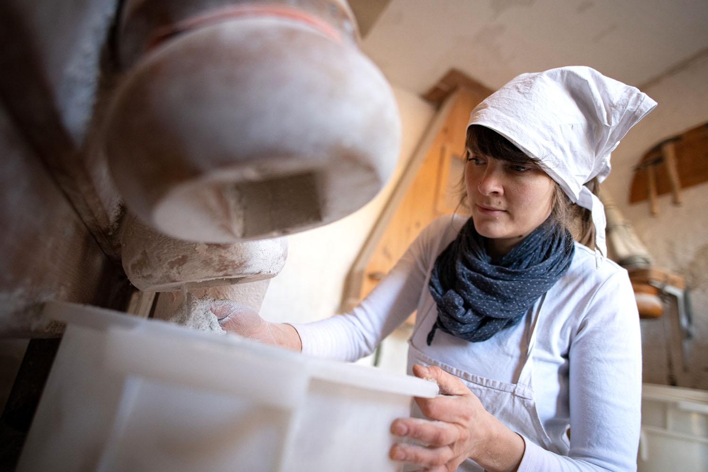 Bäckerin Verena mahlt in der Mühle Mehl für ihre Backstube