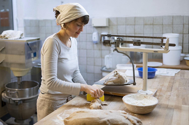Bäckerin Verena wiegt in der Backstube Teig auf der Waage ab