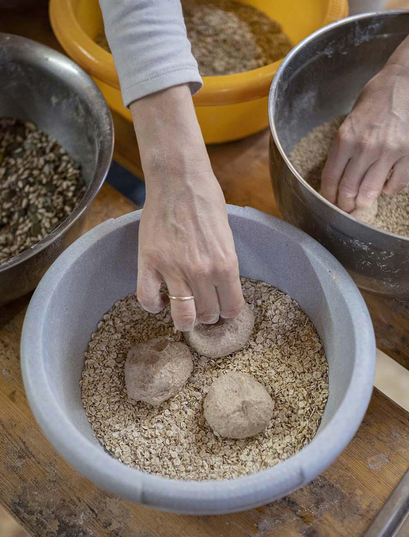 Bäckerin Verena wälzt ihre Brötchen in Haferflocken und Saaten