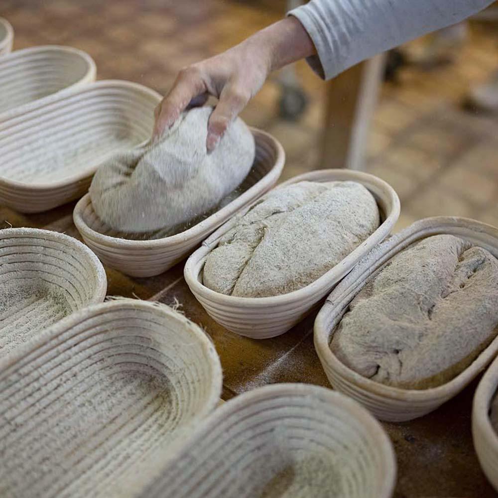 Bäckerin Verena legt in der Backstube Teiglinge in Gärkörbchen