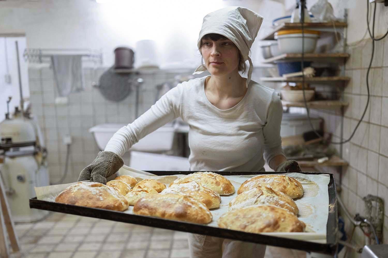 Bäckerin Verena holt in der Backstube ein Blech mit Broten aus dem Ofen