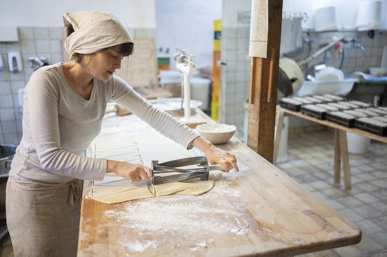 Bäckerin Verena rollt in der Backstube einen Plunderteig aus