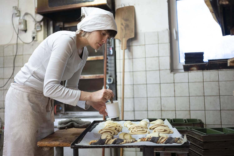 Bäckerin Verena bestreicht in der Backstube Gebäck
