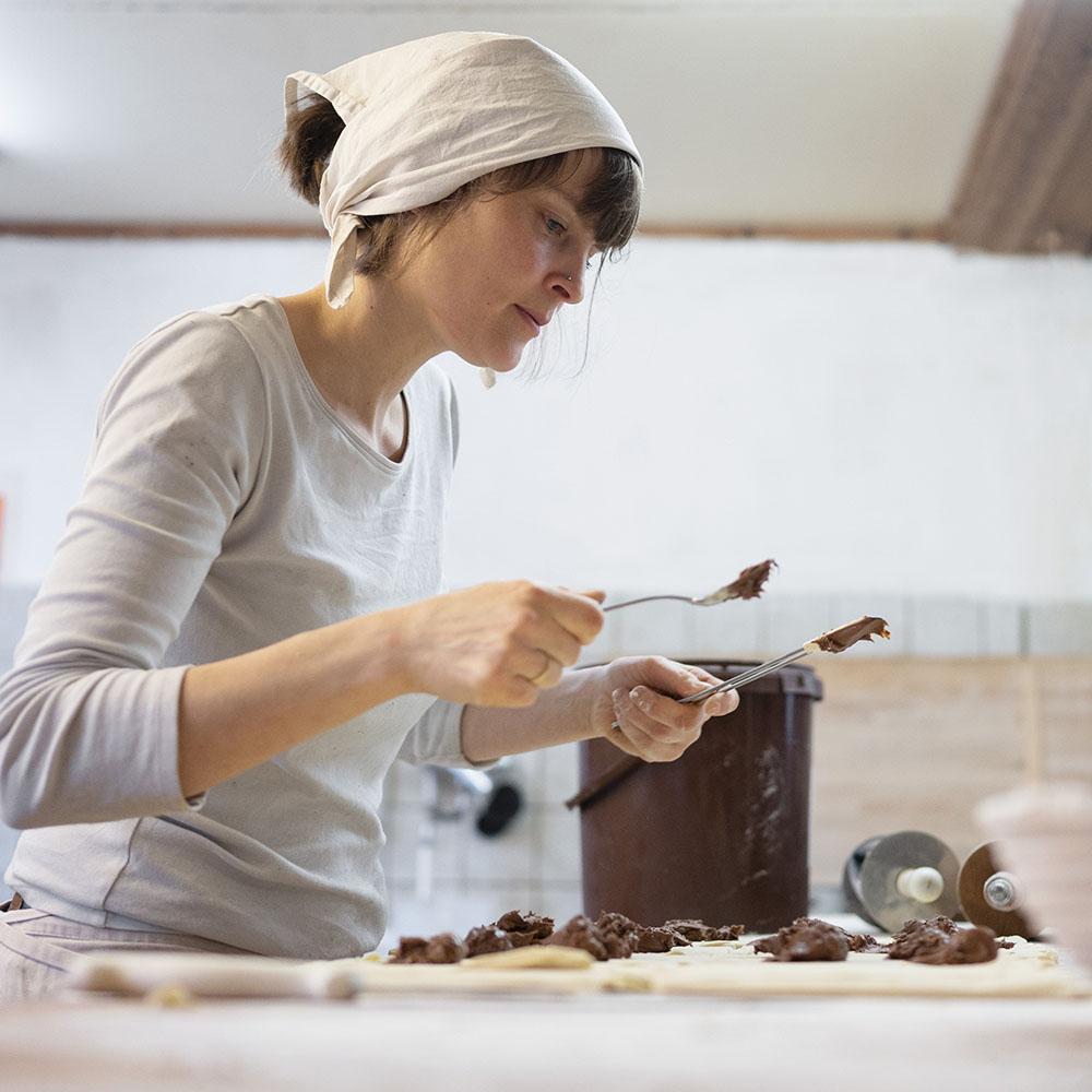 Bäckerin Verena macht in der Backstube Gebäck