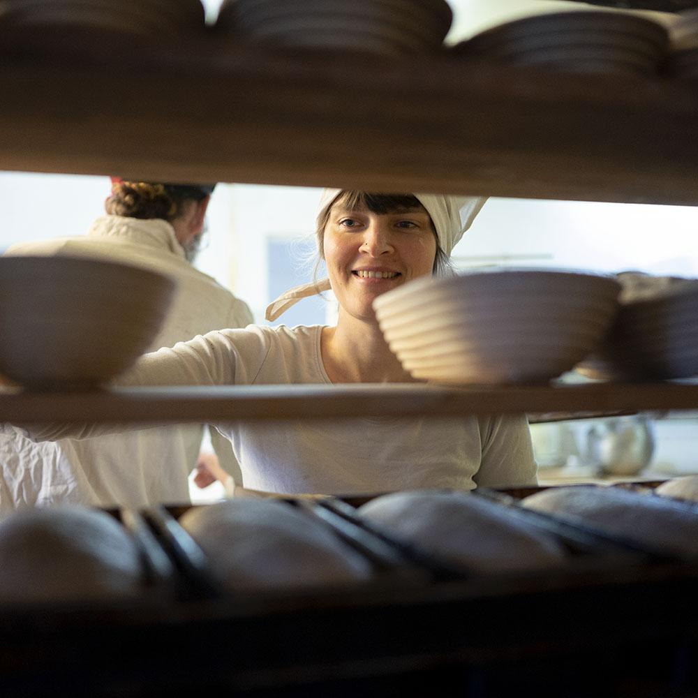 Bäckerin Verena stellt in der Backstube Gärkörbchen in ein Regal