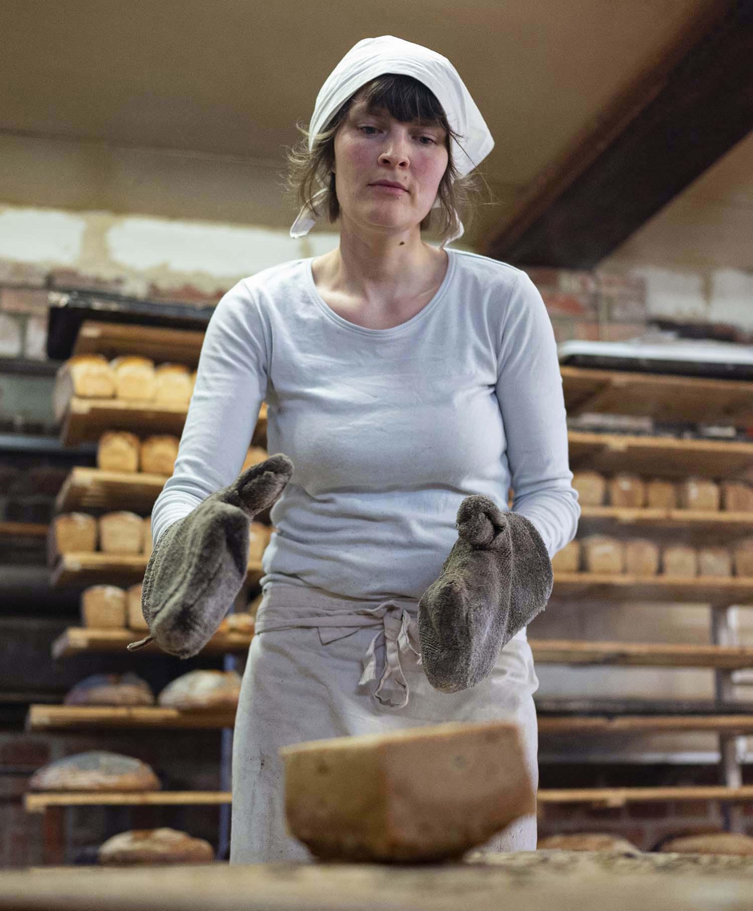 Bäckerin verena greift in der Backstube ein fertiges Brot
