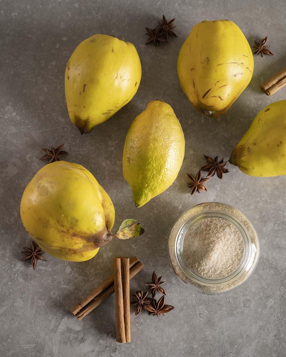 Zutaten für selbst gemachtes Quitten-Kompott: Zucker, Zitrone, frische Quitten, Zimtstangen und Sternanis