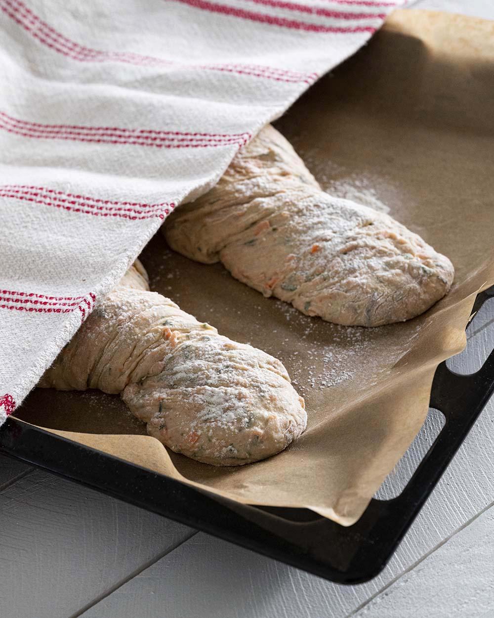 Zwei Wurzelbrote auf einem Backblech, abgedeckt mit einem Küchentuch. Die Brote sollen 30 Minuten gehen.