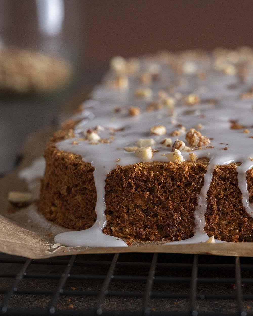 Der Möhrenkuchen mit Zitronenguss wird mit etwas Haselnusskrokant verziert