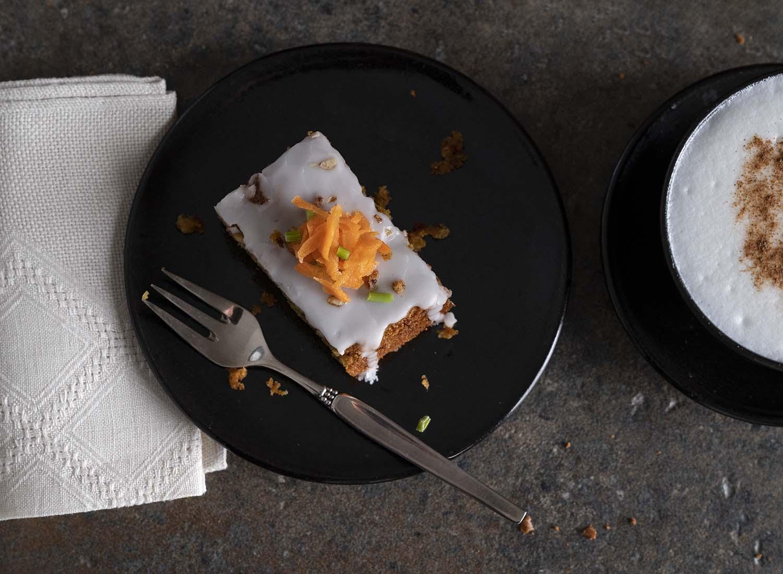 Ein Teller mit einem Stück Möhrenkuchen, fotografiert von oben