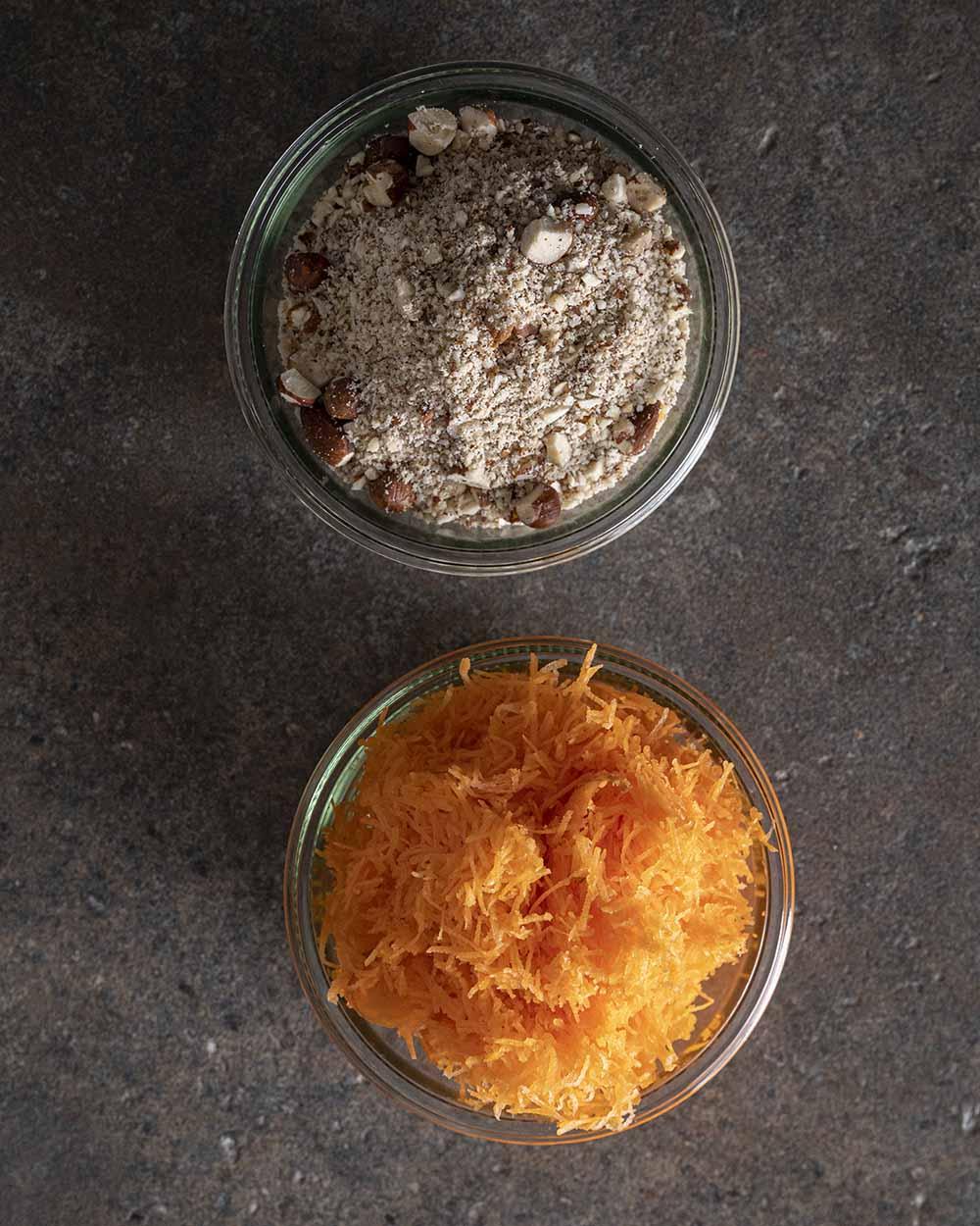 Zwei Schalen, gefüllt mit gemahlenen Nüssen und geraspelten Möhren