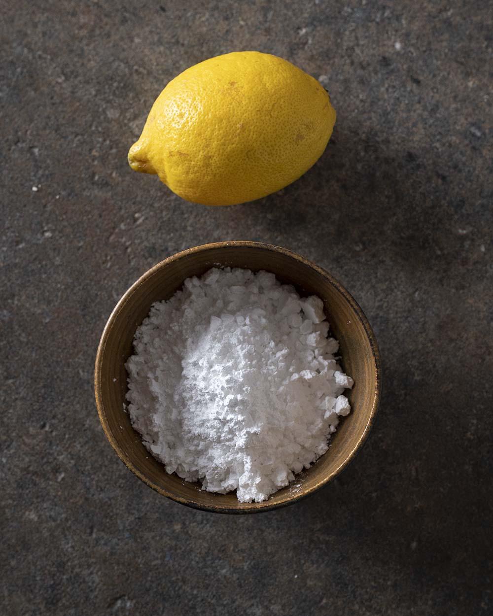 eine Itrone und eine Schale mit Puderzucker für den Zitronenguss