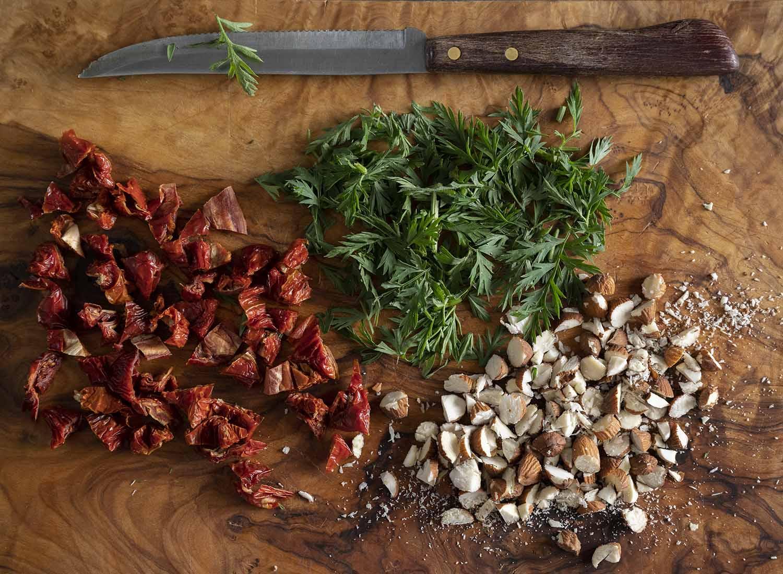 Brett mit gehackter Bundmöhre, gehackten getrockneten Tomaten und gehackten Nüssen, fotografiert von oben