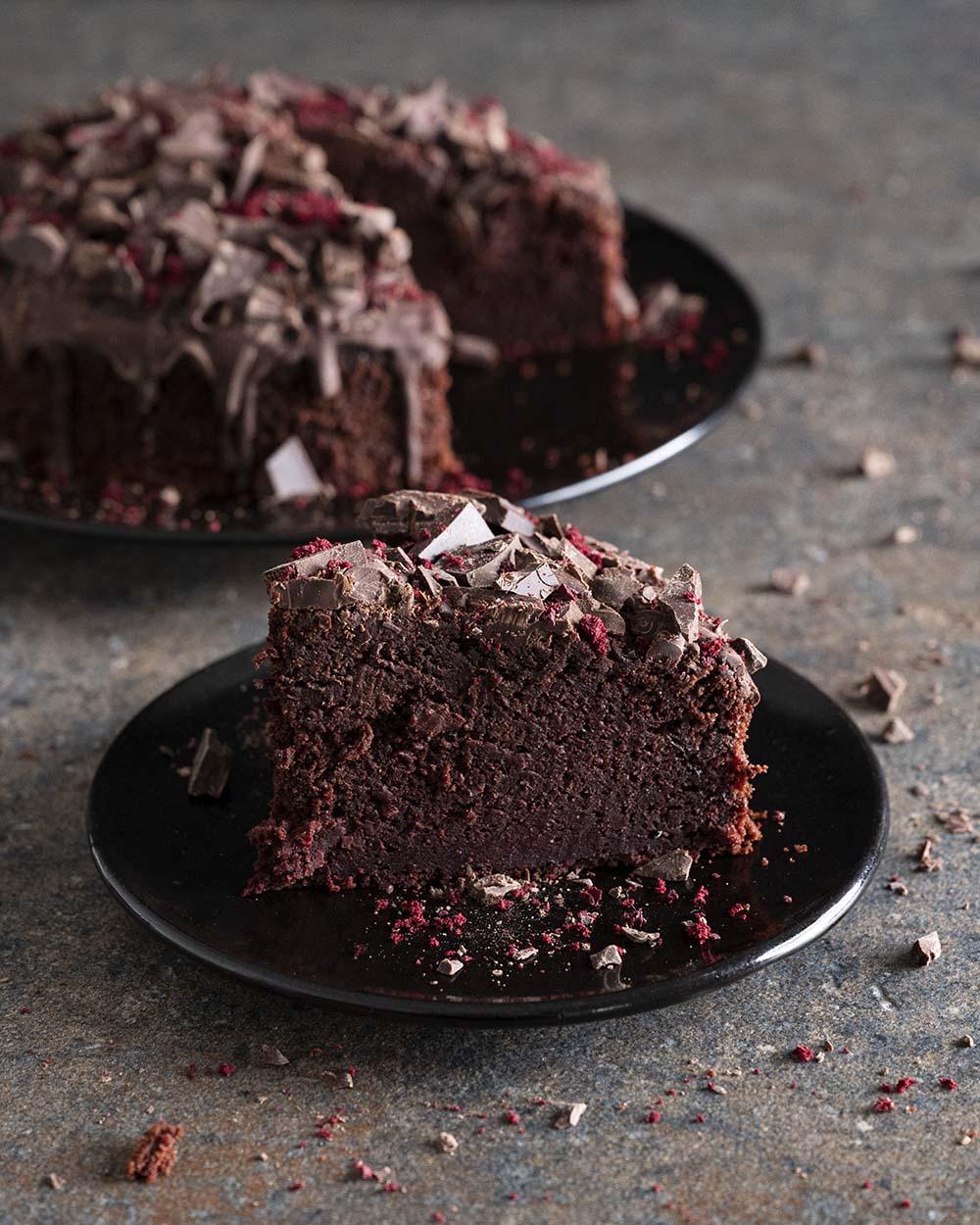 Ein Stück Rote-Bete-Schoko-Kuchen. Im Hintergrund ist der ganze Kuchen zu sehen.
