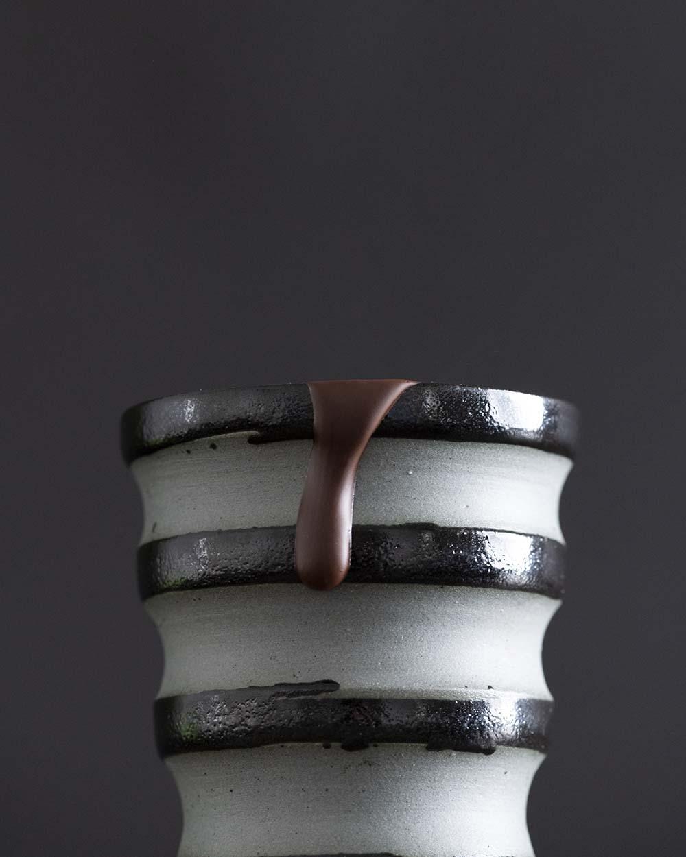 Geschmozlene Schokolade tropft von einem Becher