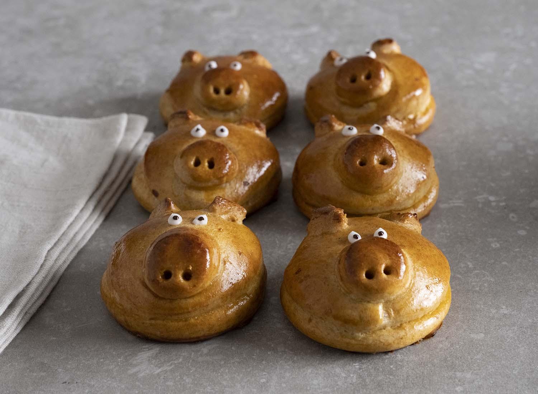 Und weil wir sie so schön finden, ein letztes Mal: Sechs Glücksschweinchen aus Hefeteig neben - und hintereinander blicken den Betrachter des Bildes an.