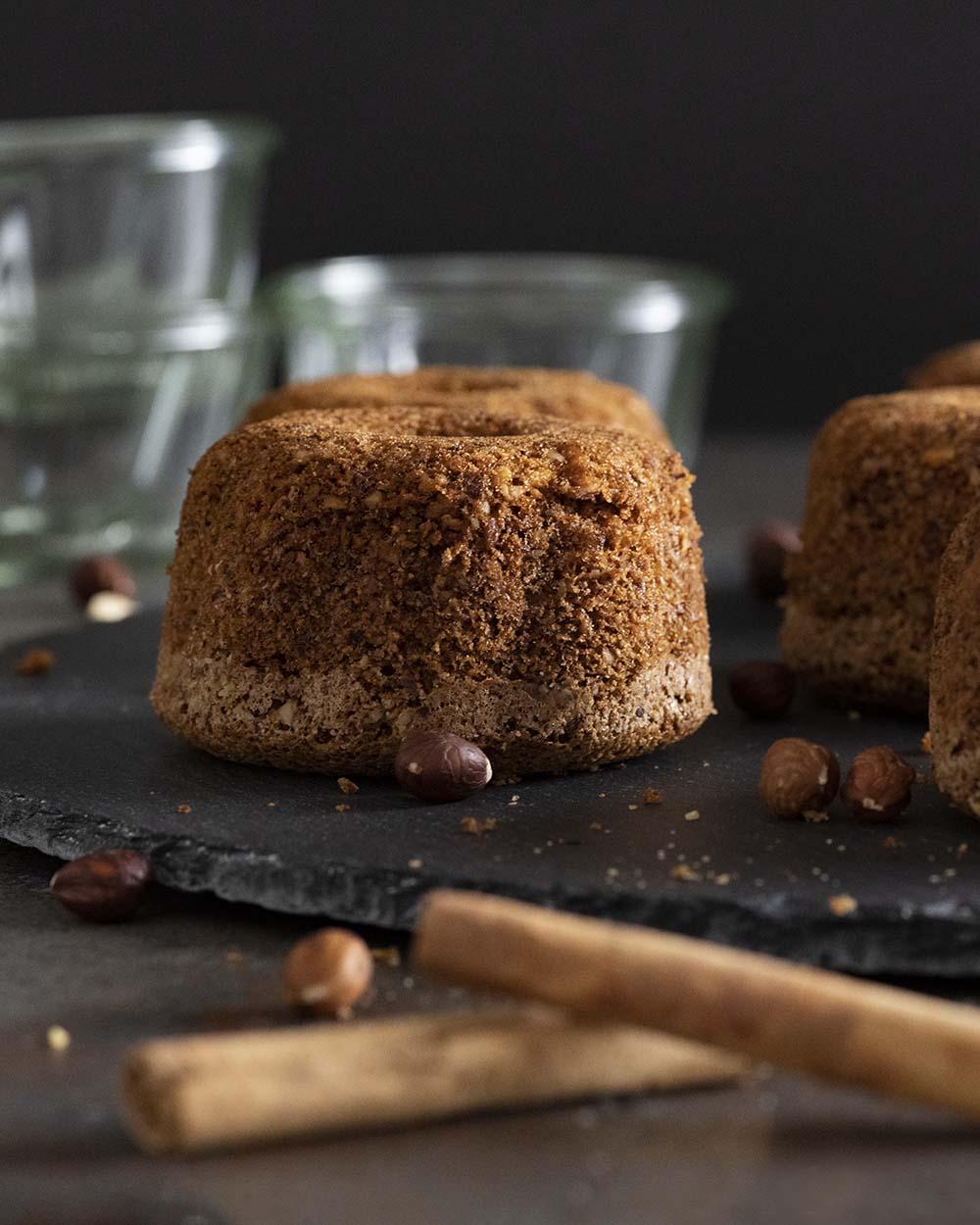 Ein fertig gebackener Nuss-Gugelhupf auf einer Kuchenplatte. Noch ist er ohne Zuckerglasur.