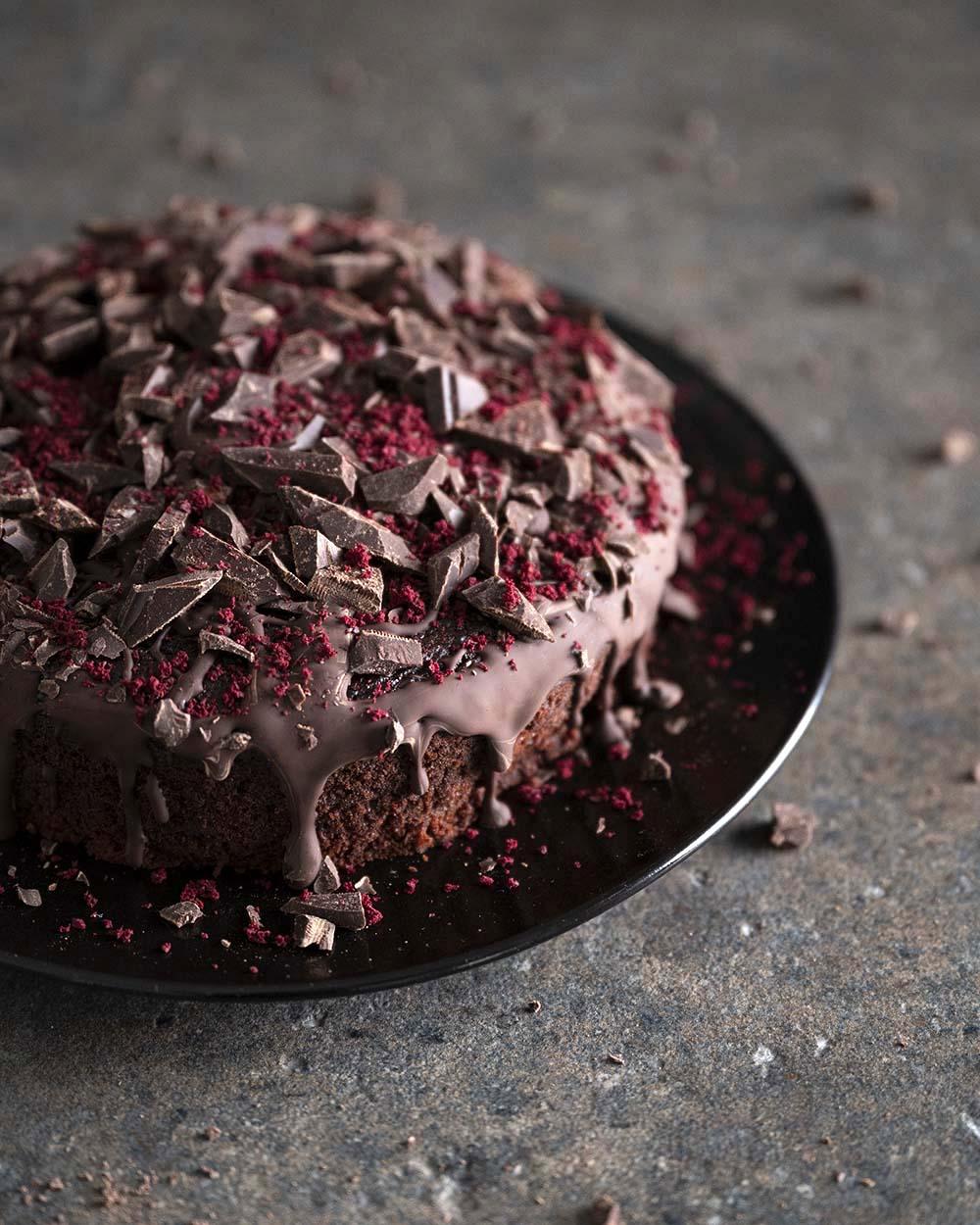 Draufsicht auf die Oberfläche unseres Rote-Bete-Schoko-Kuchens, jetzt glasiert und mit Schokoladenstückchen und Rote Bete Granulat verziert