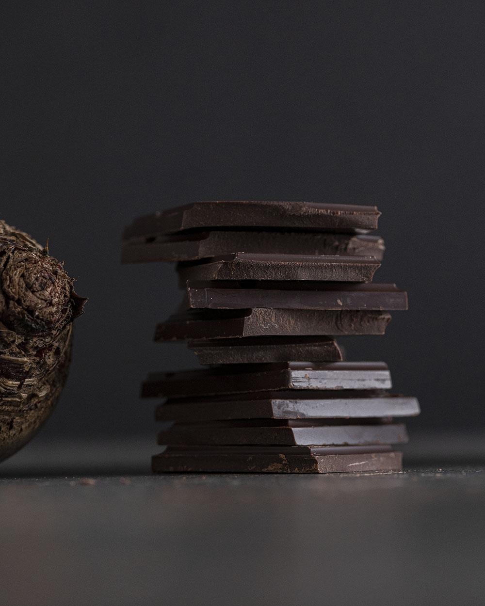 Eine Knolle Rote Bete liegt neben einem Stapel aufgetürmter Schokoladenstückchen