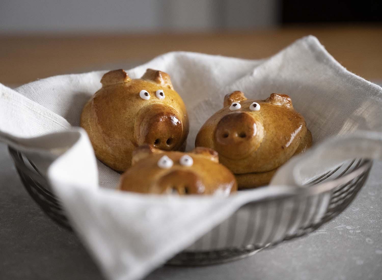 Drei Glücksschweinchen aus Hefeteig liegen in einem Brotkorb