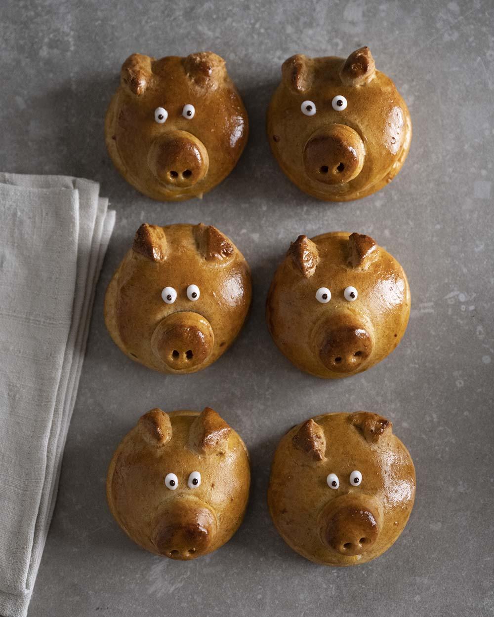 Sechs Glücksschweinchen aus Hefeteig, liegen nebeneinander. Wir haben sie von oben fotografiert.