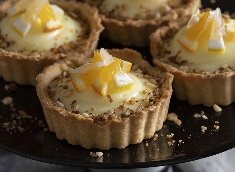 Nahaufnahme eines Tartelettes mit Vanillecreme. Als Dekoration haben wir kleine Scheiben Zitrusfrüchte gewählt.