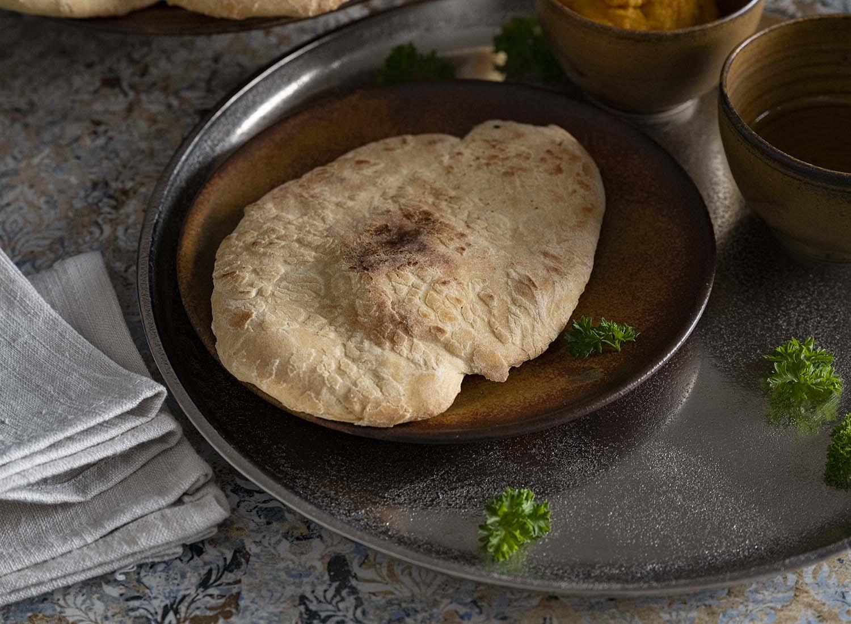 Nahaufnahme eines unserer sechs Naan Brote. Es liegt auf einem Teller, im Hintergrund sind die Schalen mit Öl und Dip zu sehen.