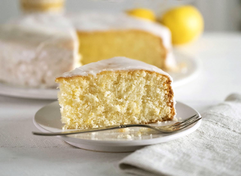 Ein Stück saftiger Zitronenkuchen auf einem Teller. Der Fokus liegt auf der schönen, fluffigen Porung.