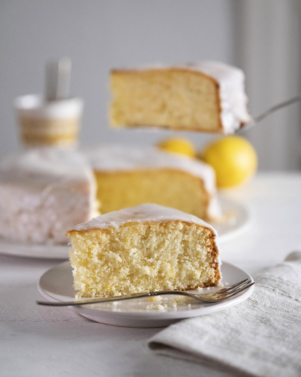 Im Vordergrund ist ein Stück Zitronenkuchen auf dem Teller zu sehen. Im Hintergrund heben wir ein zweites Stück aus dem ganzen Kuchen heraus.
