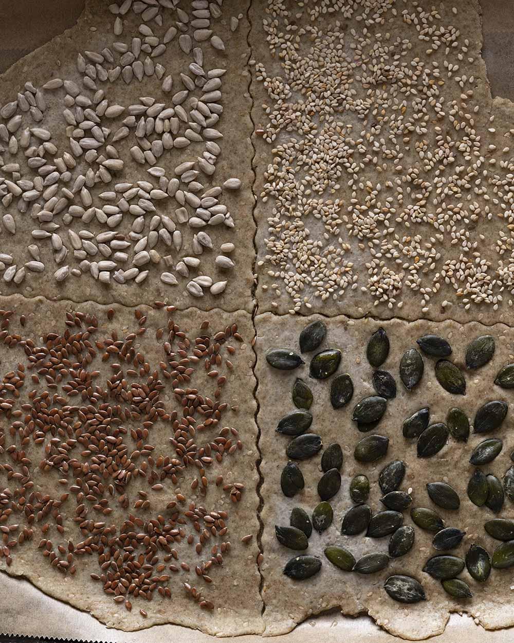 Der ausgerollte Teig für unser Knäckebrot auf dem Backblech. Wir haben ihn mit verschiedenen Zutaten belegt, darunter Kürbiskerne und Leinsamen.