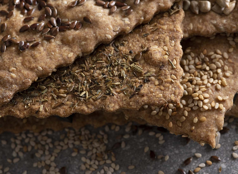 Nachaufnahme des Stapels Knäckebrot. Zu sehen sind Scheiben mit Leinsamen, Kärutern, Sonnenblumenkernen und Sesam.
