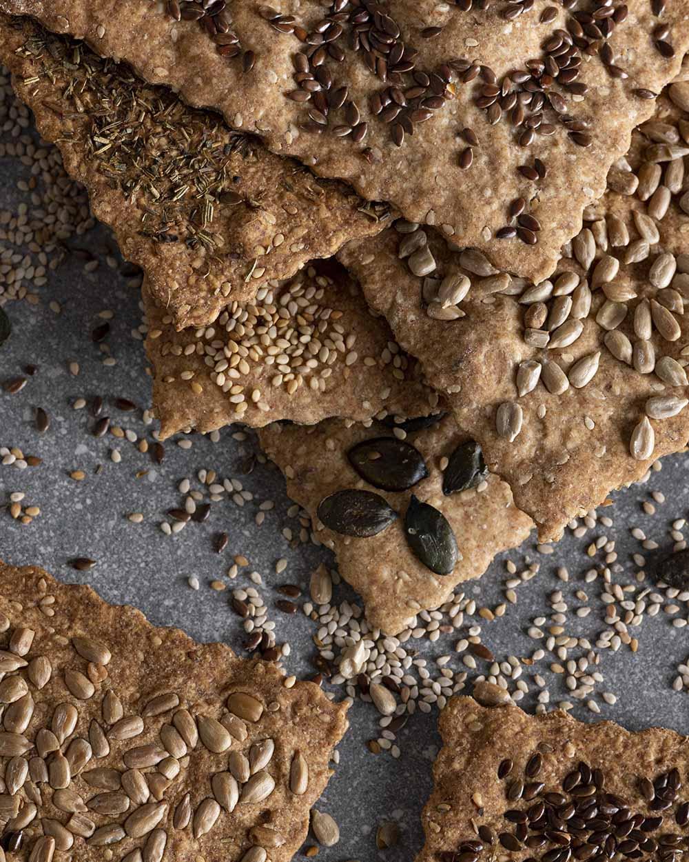 Mehrere Scheiben unseres selbst gemachten Knäckebrots. Zu sehen sind Scheiben mit unterschiedlichen Saaten und Kräutern.