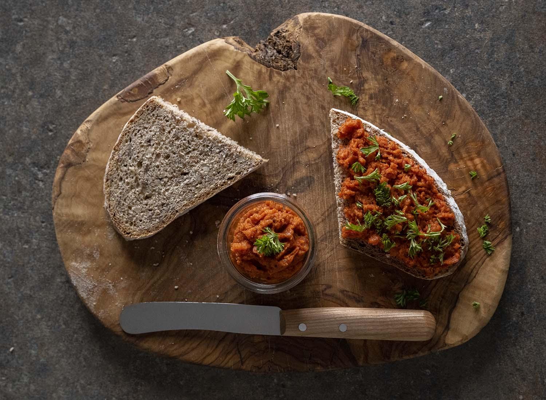 Das Frühstücksbrett mit allen Zutaten, darunter einer bestrichenen Scheibe Brot, fotografiert von oben.
