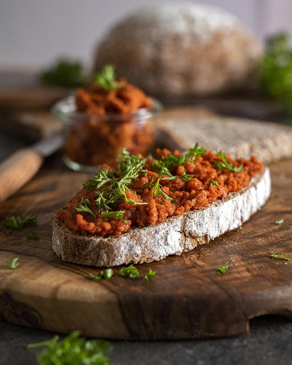 Auf dem Bild ist eine Scheibe Brot zu sehen, die wir mit unserem herzhaften Möhren-Dip bestrichen haben. Garniert haben wir sie zusätzlich mit frischer Petersilie.
