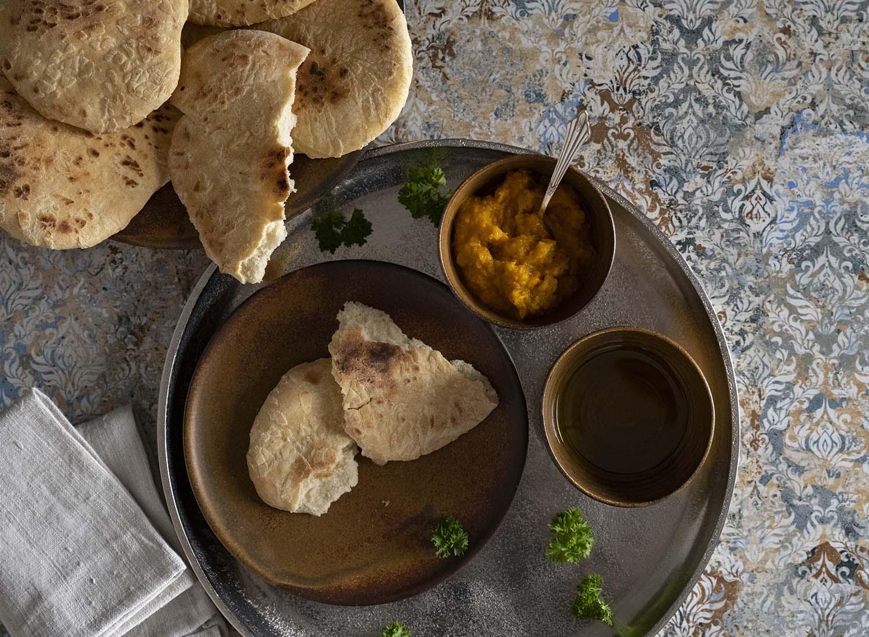 Fertig gebackenes Naan Brot, serviert auf einem silbernen Tablett. Das erste Brot haben wir aufgebrochen. Daneben stehen zwei Schüsseln mit Öl und einem Kürbis-Dip