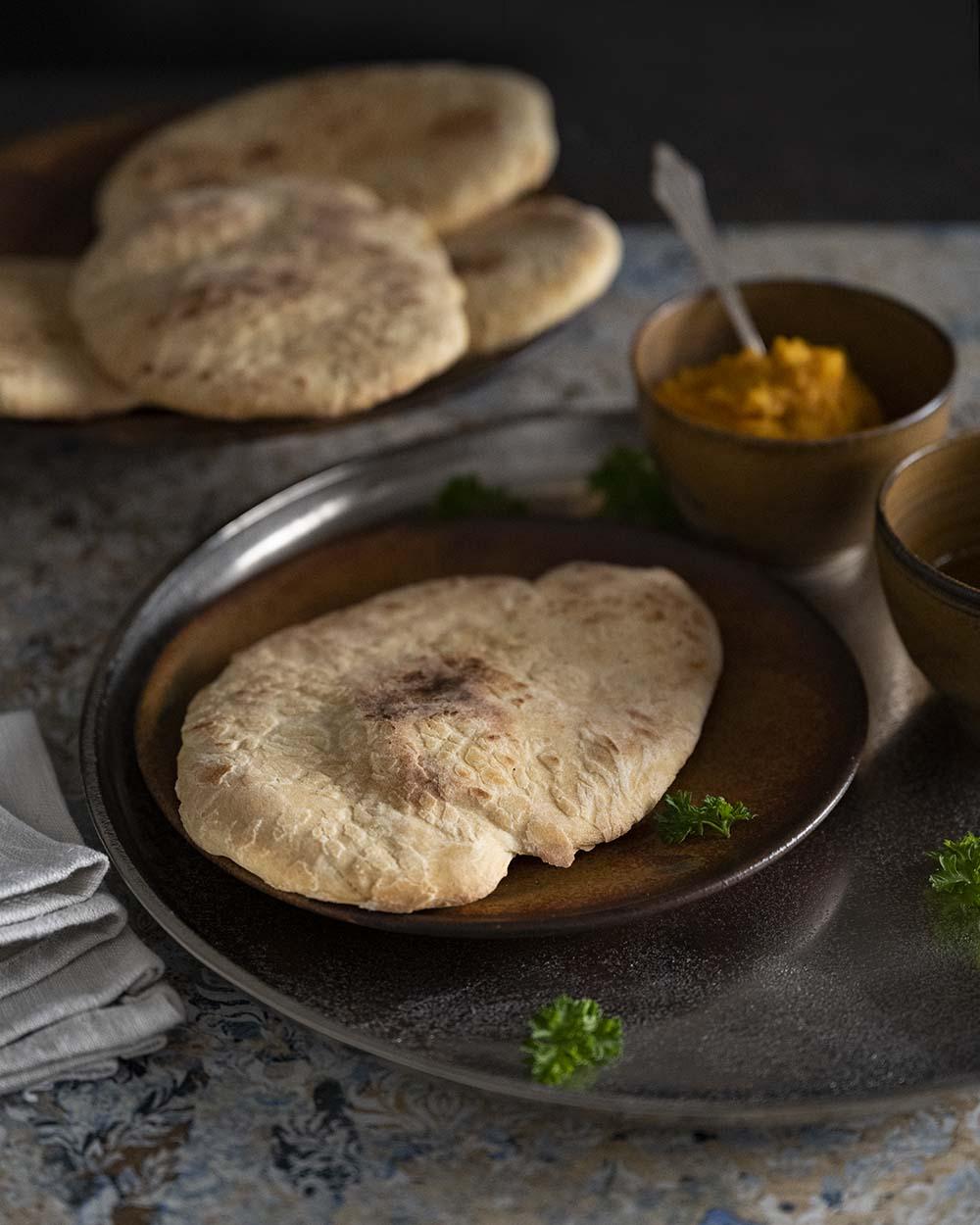Das Naan Brot ist fertig gebacken und liegt auf einem Teller. Im Hintergrund sind Schalen mit Öl und Dip zu sehen.