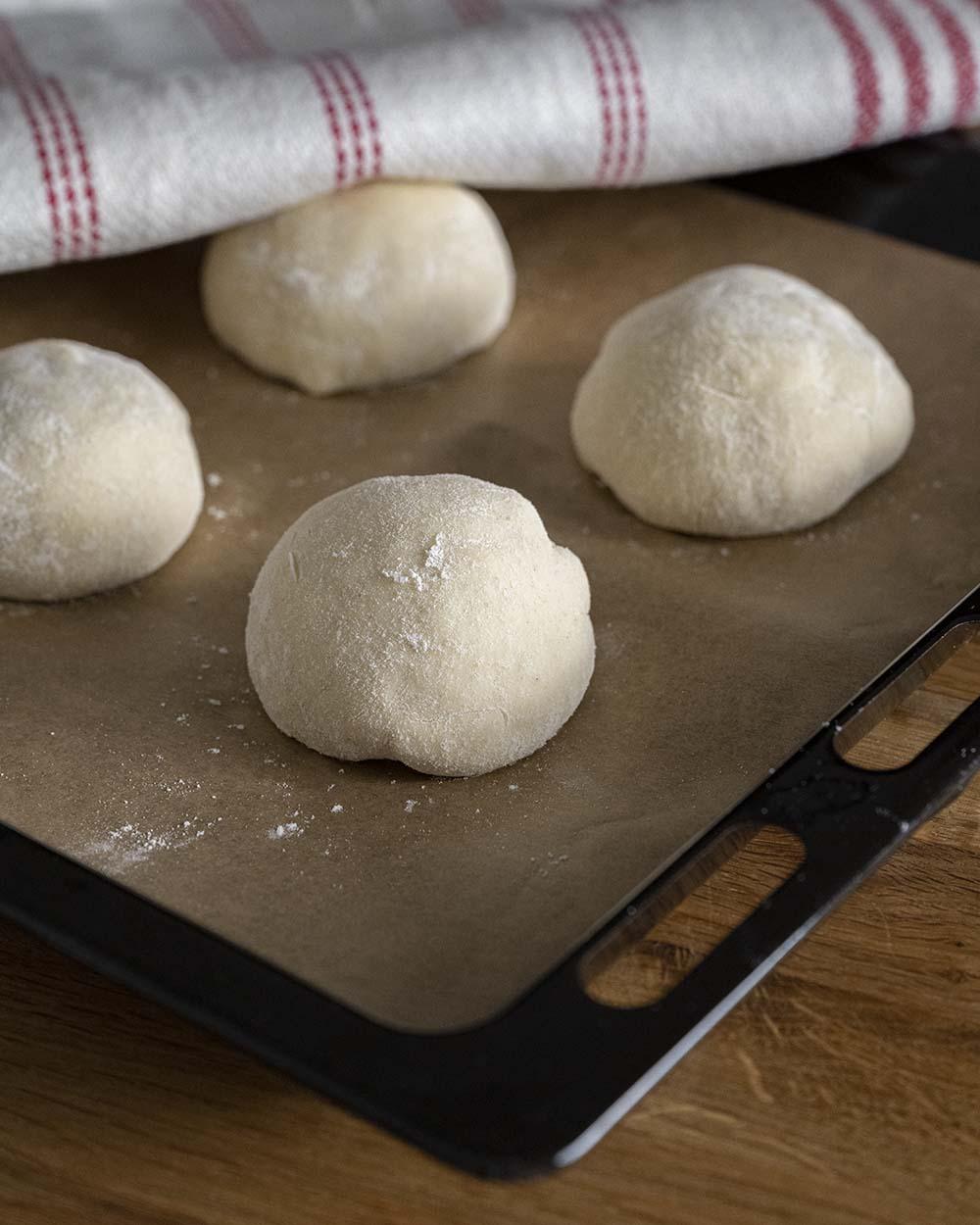 Einzelne Kugeln Teig liegen auf einem Backblech und werden gleich mit einem Handtuch abgedeckt, damit das Naan Brot gut gehen kann.