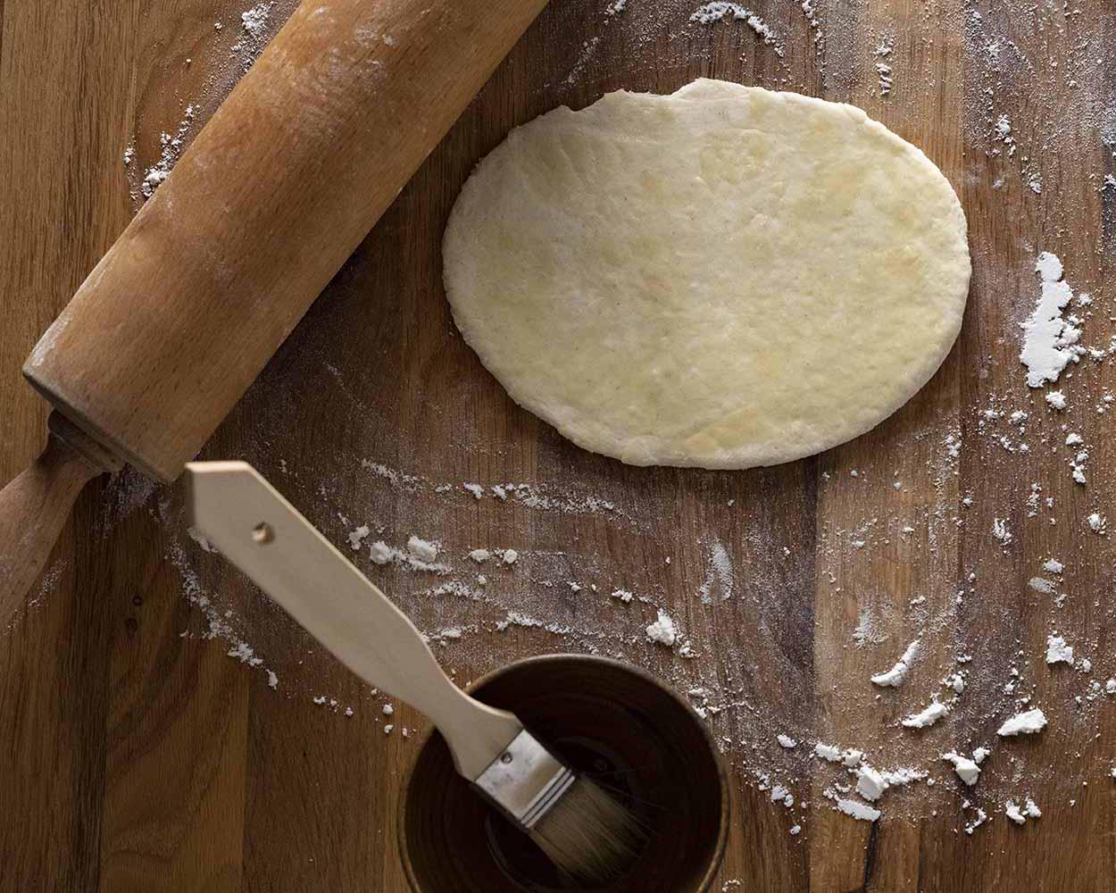 Wir streichen das erste Naan Brot vor dem Backen auf der Oberfläche mit etwas Öl ein.