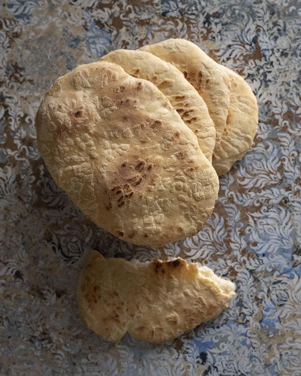 Mehrere Naan Brote, die gerade frisch aus dem Ofen gekommen sind, liegen auf einem Tisch.