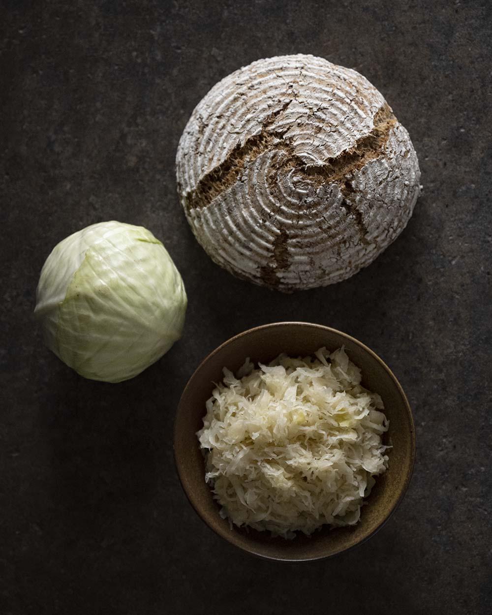 Ein Foto von oben: Zu sehen sind darauf ein Kopf Weißkohl, eine Schale mit frischem Sauerkraut und ein fertig gebackenes Sauerkrautbrot.