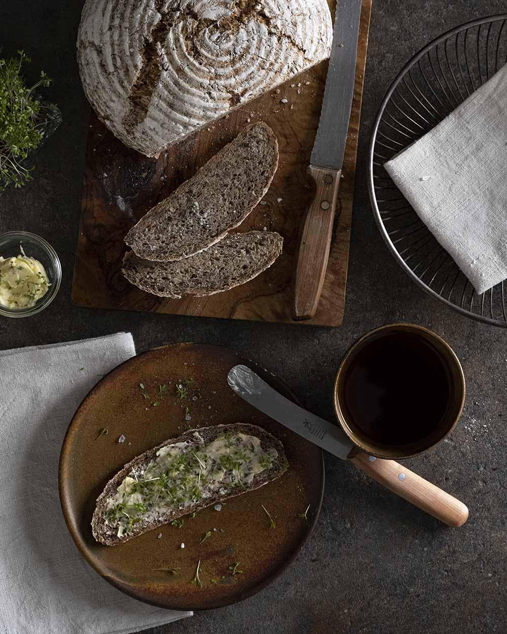 Eine Scheibe Sauerkrautbrot auf einem Teller. Wir haben es mit Butter bestrichen und Kresse darauf gestreut.