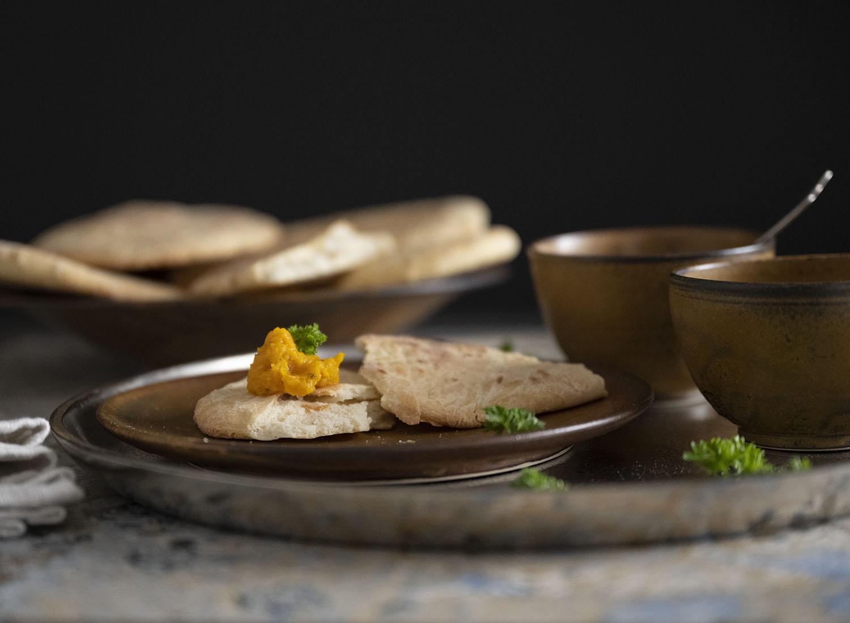 Ein weiter aufgefasstes Bild des angerichteten Naan Brots. Auf dem silbernen Tablett stehen ein Teller mit Naan Brot, daneben sind zwei Schalen mit Öl und Dip zu sehen. Im Hintergrund haben wir weitere fertig gebackene Naan Brote drapiert.