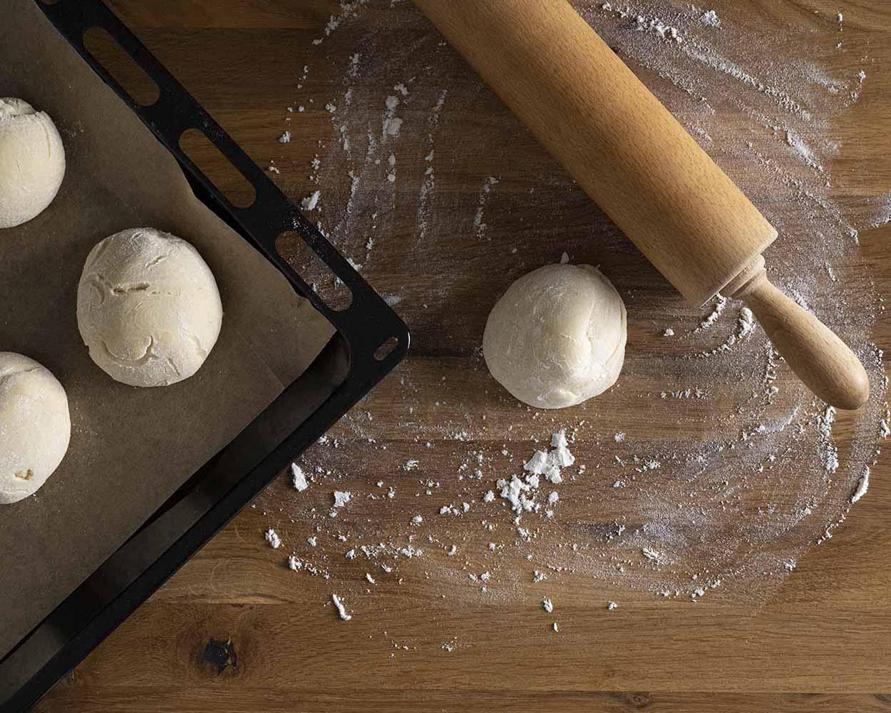 Die erste Kugel liegt auf einer bemehlten Fläche und wird gleich zu einem länglichen Naan Brot ausgerollt. Zu sehen ist auch das Nudelholz.